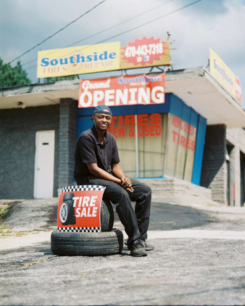 posing on tires outside of mechanic shop