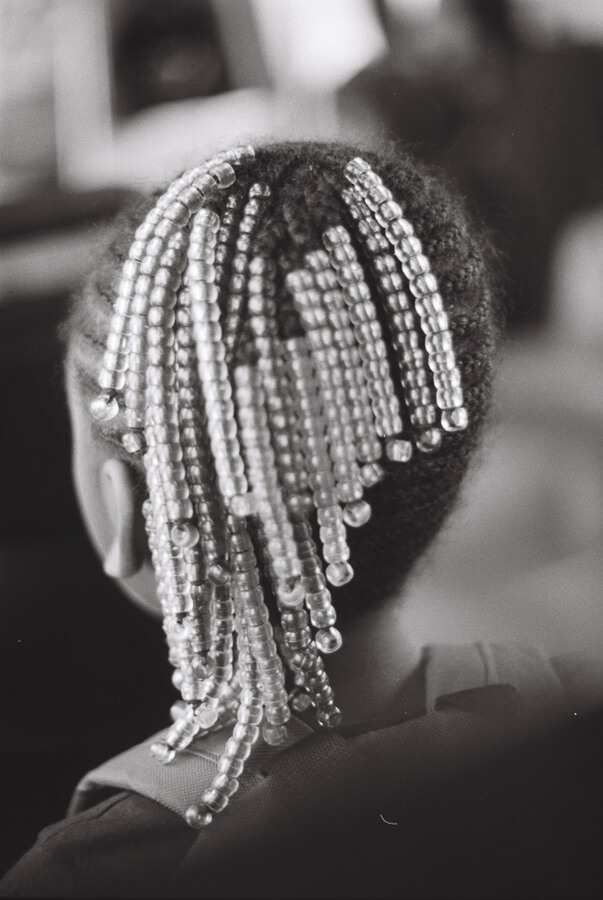 Young black girl riding the train with beads in her hair.