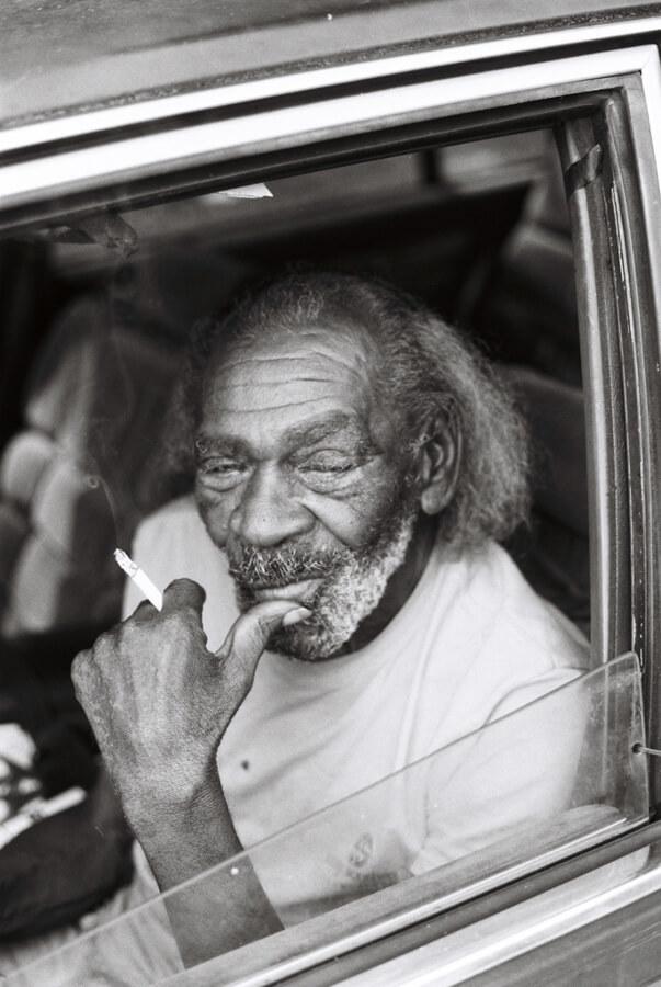 Black man sitting in Oldsmobile holding cigarette