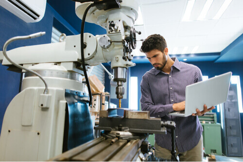 Young male working on manufacturing machine