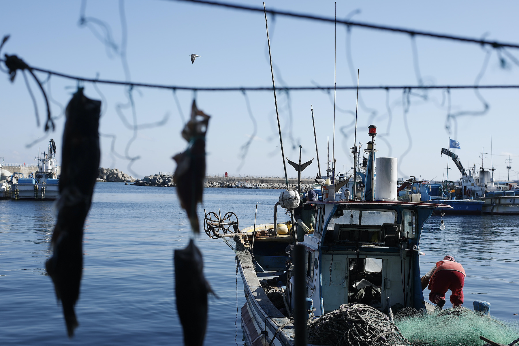 A resident of Yangyang, South Korea, cleans her fishing boat
