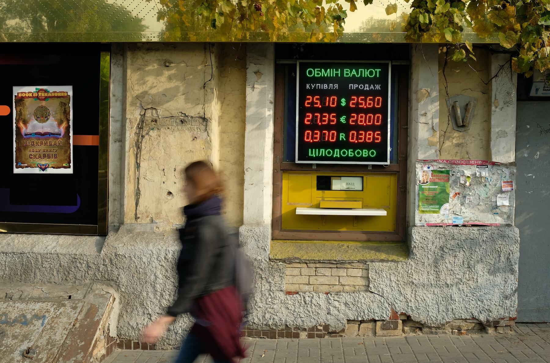 An illuminated sign advertises exchange rates