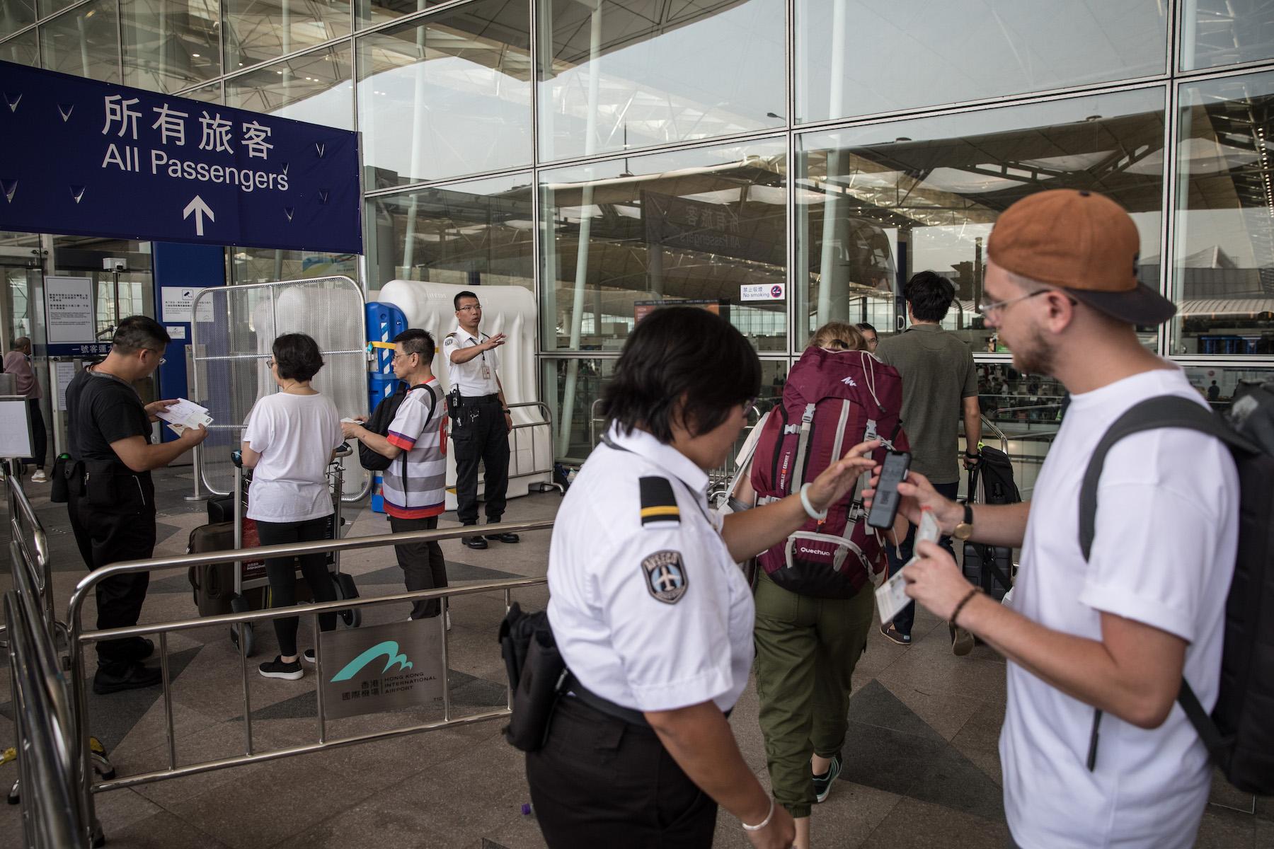 Security staff check passengers boarding passes at the entrance of Hong Kong International Airport