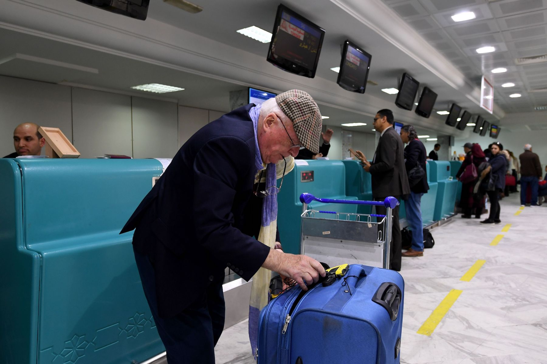 A British traveler packs his phones in his suitcase before boarding his flight for London at Tunis-Carthage International Airport