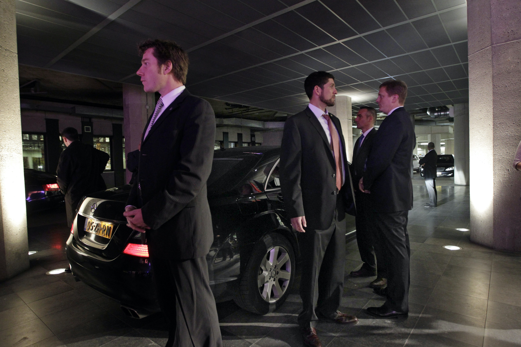 U.S. security agents stand guard at the limo of US Secretary of State