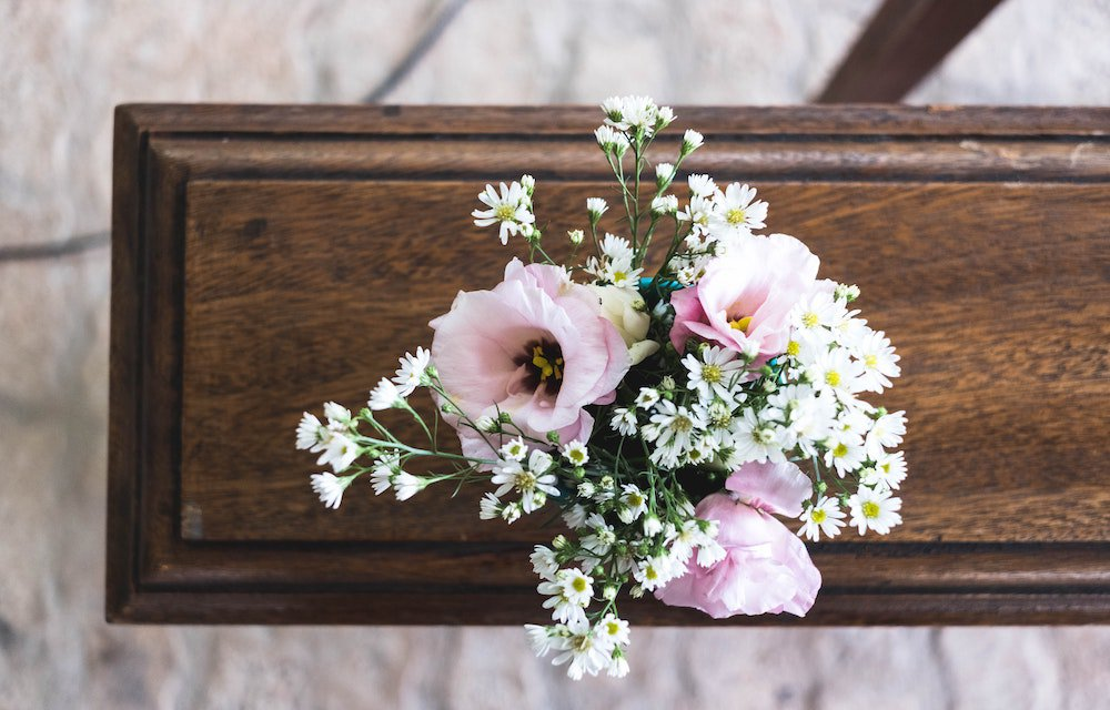 Casket with pink and white flower wreath