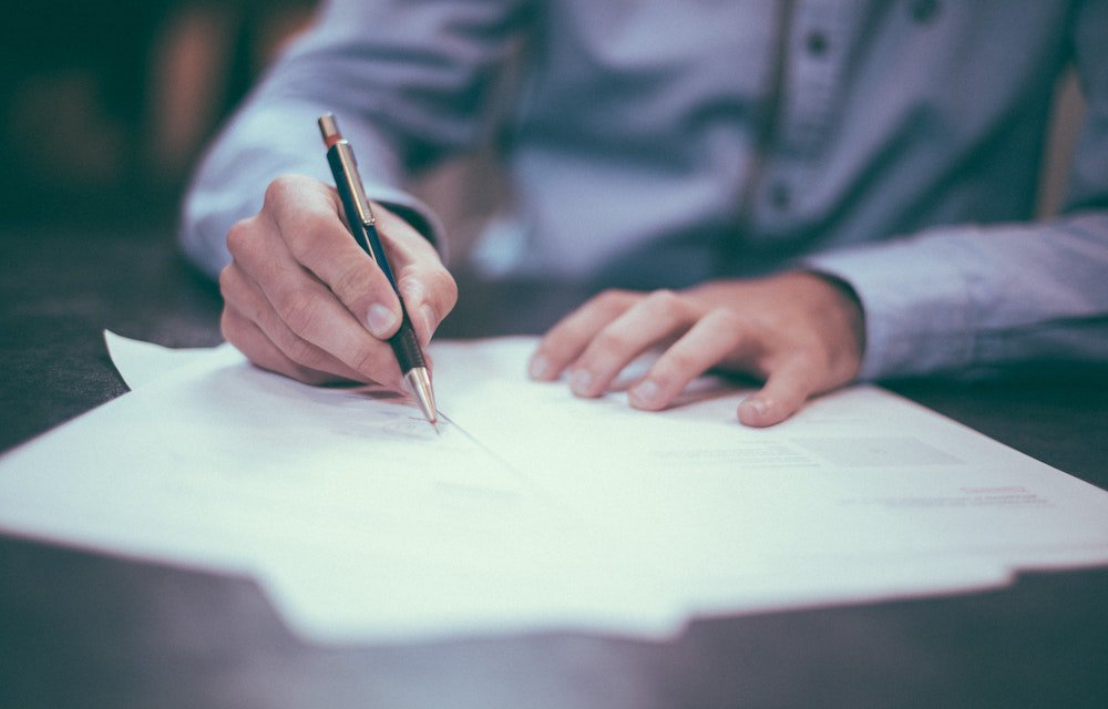 Man in blue shirt signing papers with black pen