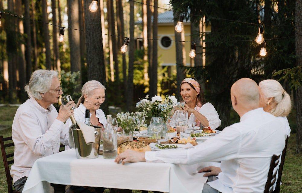 Older people enjoying themselves having dinner outside amongst trees