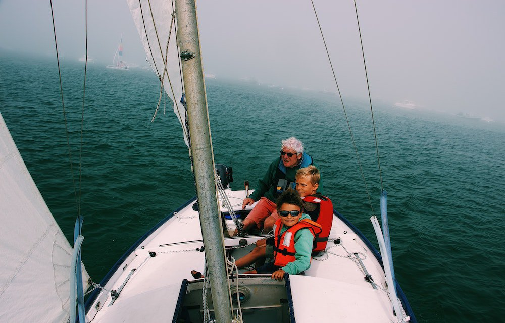 Grandfather with 2 young boys on sailing boat