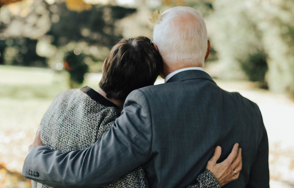 Back of older man and woman hugging