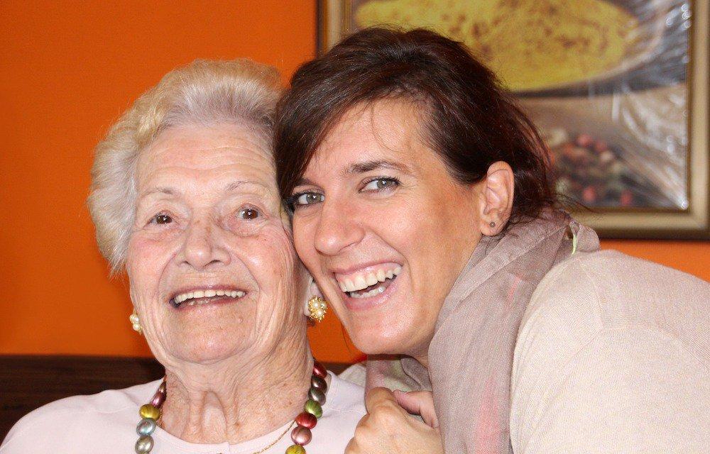 Smiling lady hugging older smiling woman next to orange wall