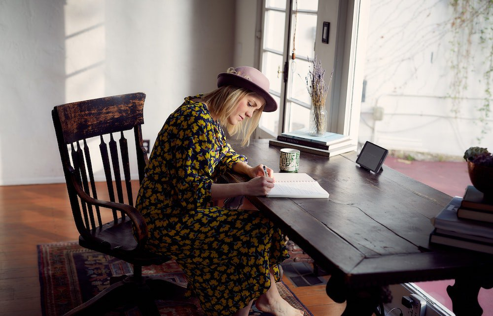 Lady in yellow flower dress and pink hat writing in notebook at wooden desk
