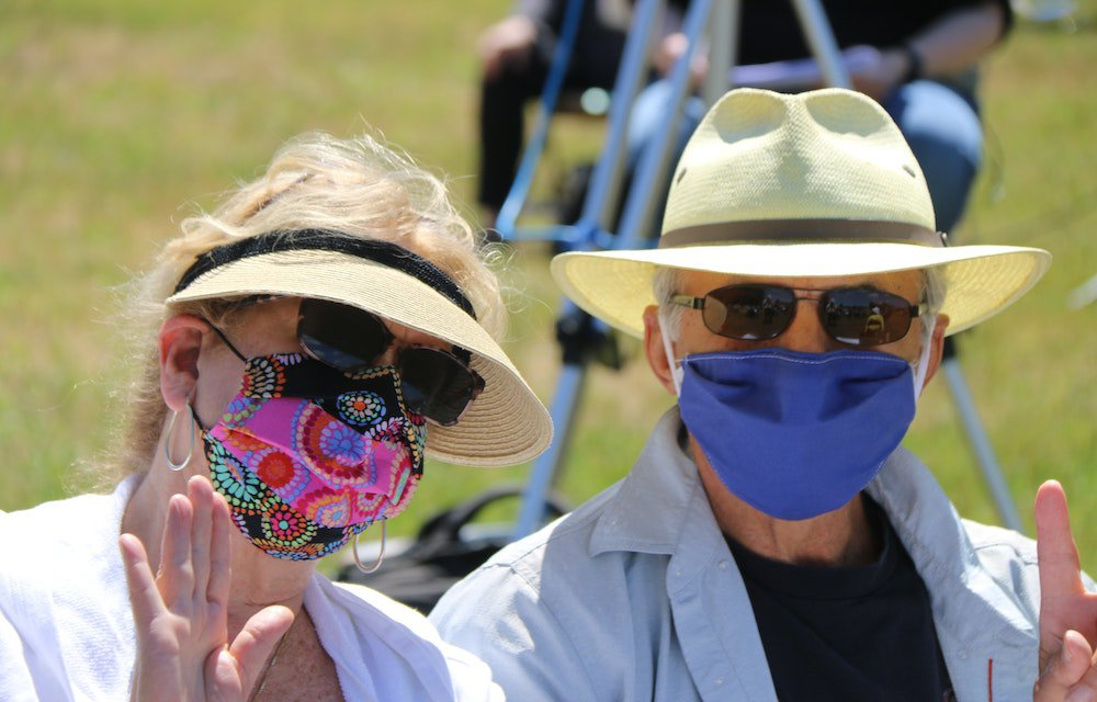 Lady and man wearing hats sunglasses and masks