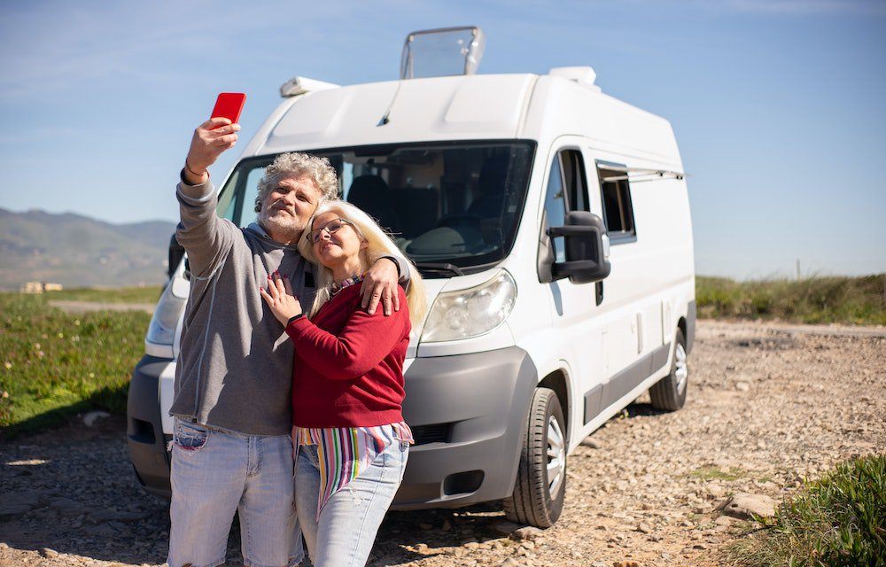 Mature couple travelling with van taking photo