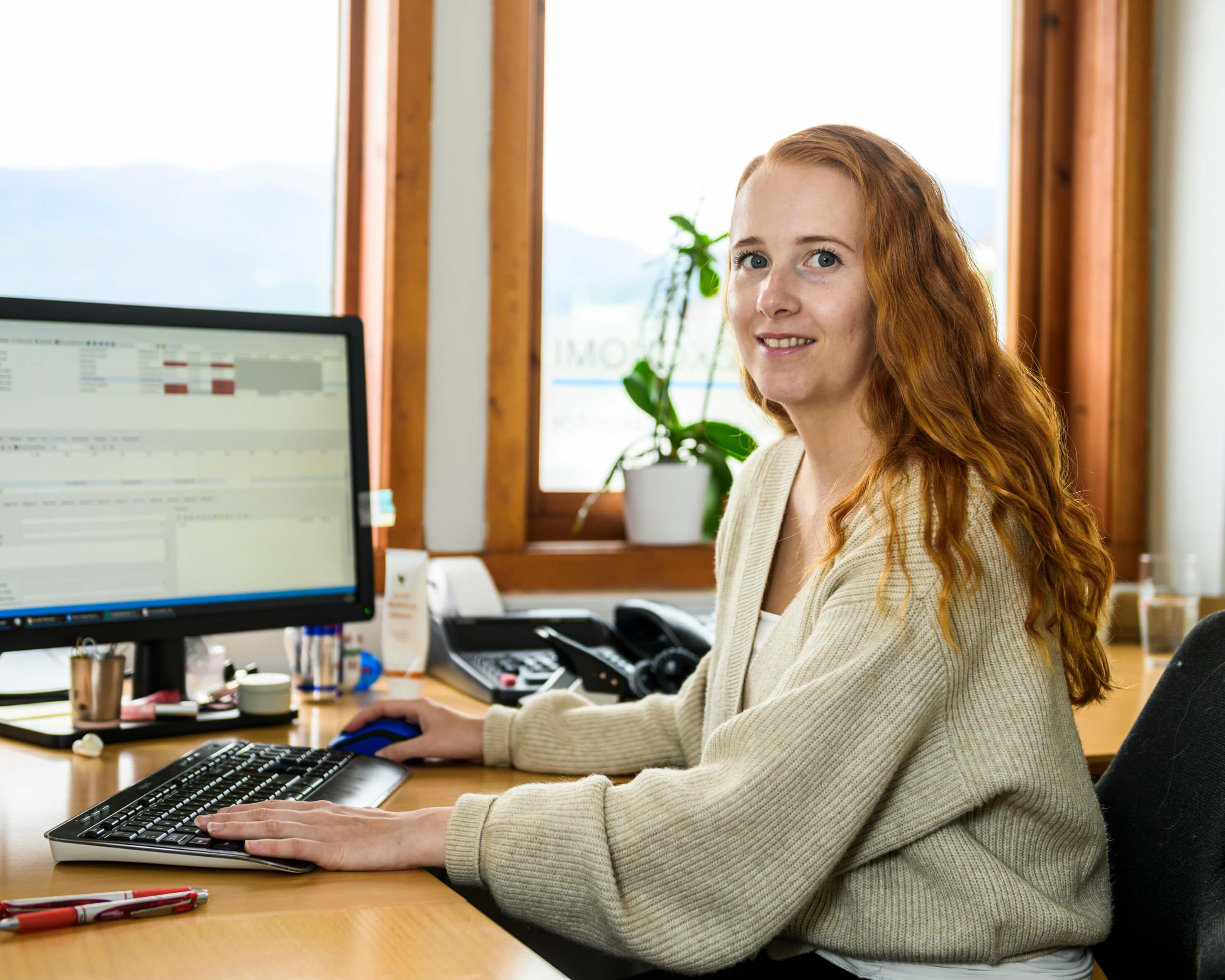 Kvinne ved kontorpult foran pc skjerm