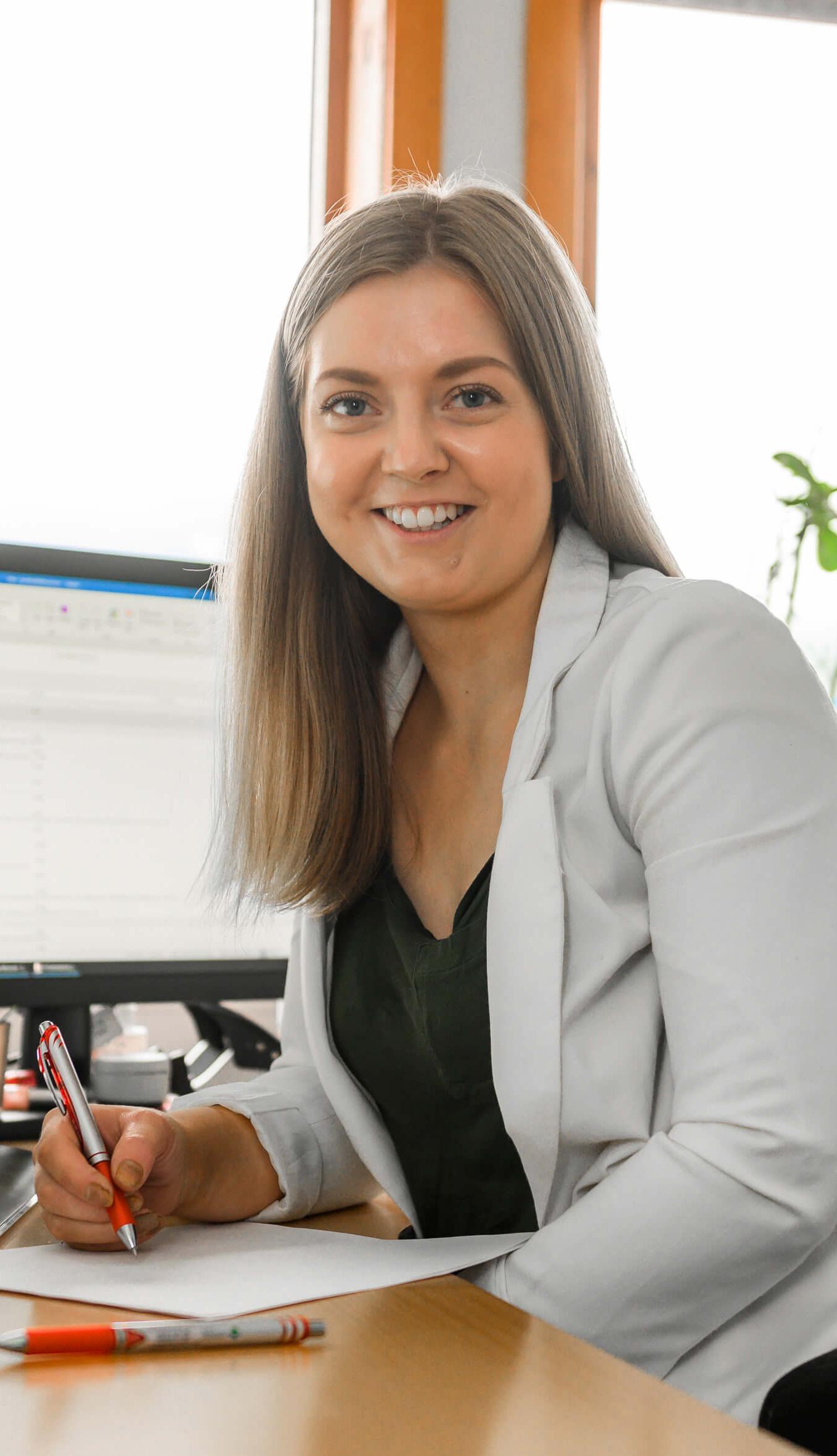 Kvinne med penn ved kontorpult foran pc skjerm.