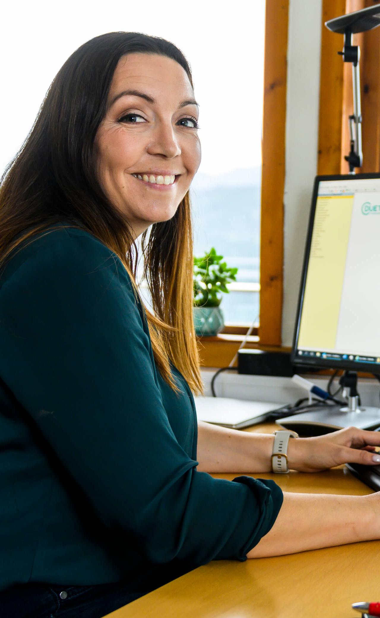 Kvinne ved kontorpult foran pc skjerm.