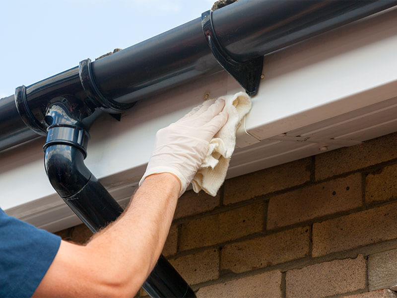 Man with gloved hand wiping gutters