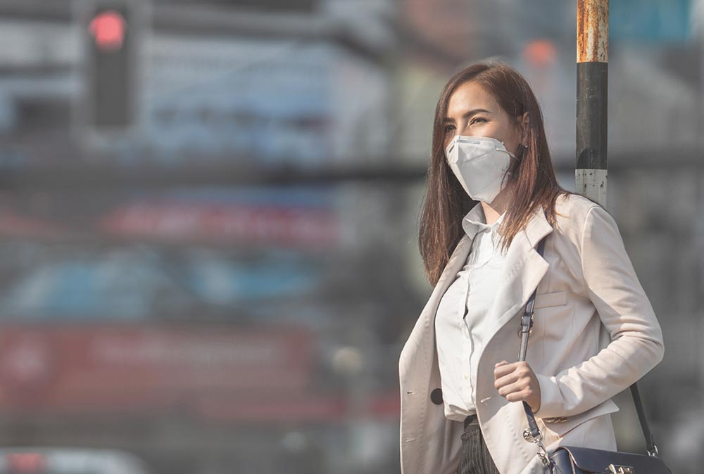 A lady in a mask within a city that uses Clarity Nodes for ambient air quality monitoring