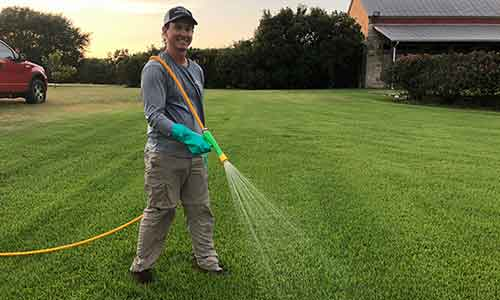 Greener LawnScapes team member performing a scheduled weed control treatment for a homeowner in Bryan, TX.