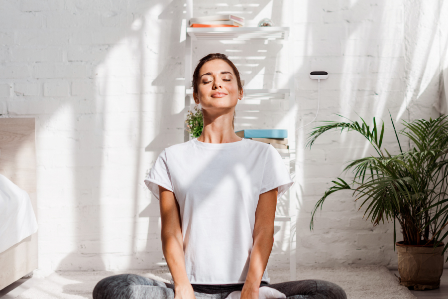 Woman doing yoga in a comfortable room thanks to Ambi Climate