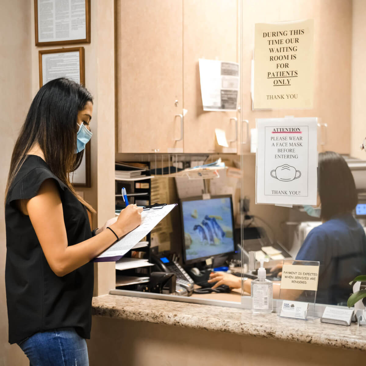 patient signing form at front office
