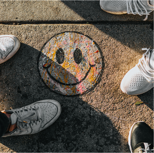 Smiley face image with people standing around it