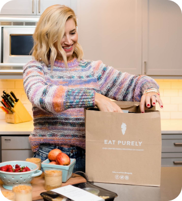 woman with Eat Purely packaging in her kitchen