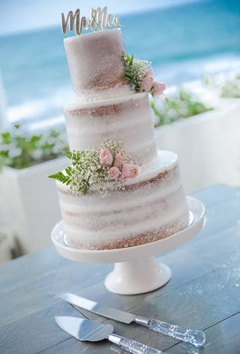 A wedding cake on a table overlooking the ocean