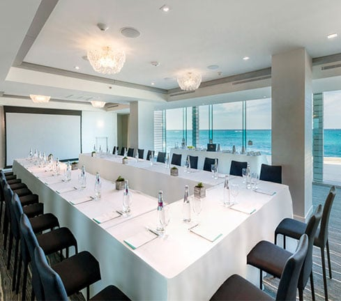 A meeting area with a large U shaped table and ocean views