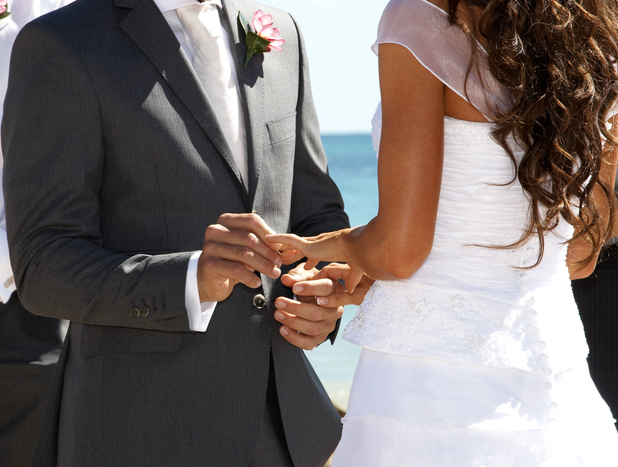 A man putting a ring on a womans hand in front of ocean