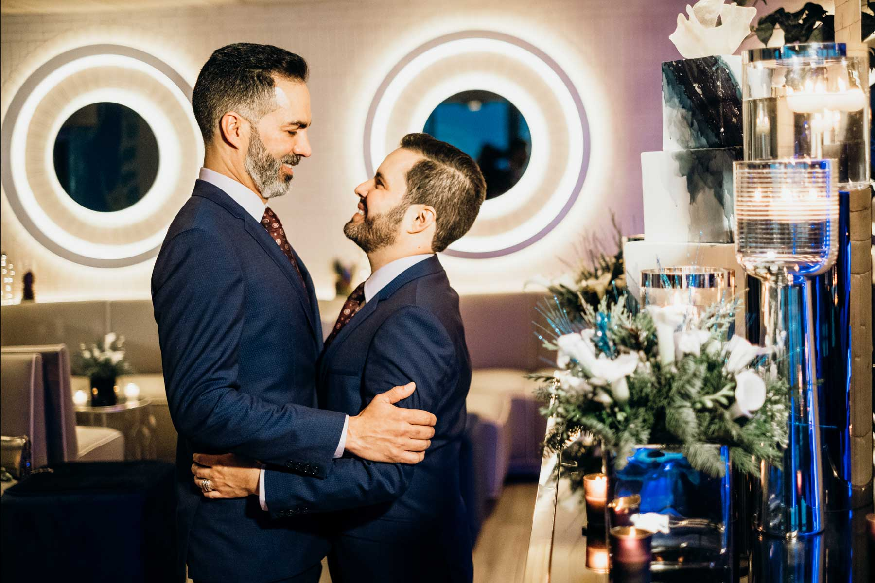 Two men in suits embracing in decorated room