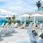 Outdoor seating overlooking beach with umbrellas and bucket of champagne