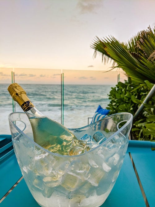 A bottle of champagne on ice on a blue table overlooking the ocean