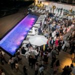 Outdoor gathering of people around the pool at Condado Ocean Club
