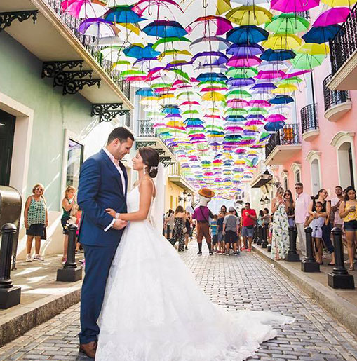 A couple on a street under a bunch of umbrellas in wedding attire
