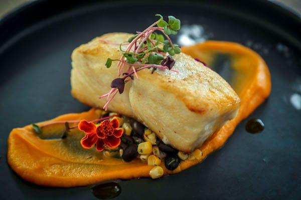 A closeup of a seafood and orange sauce dish