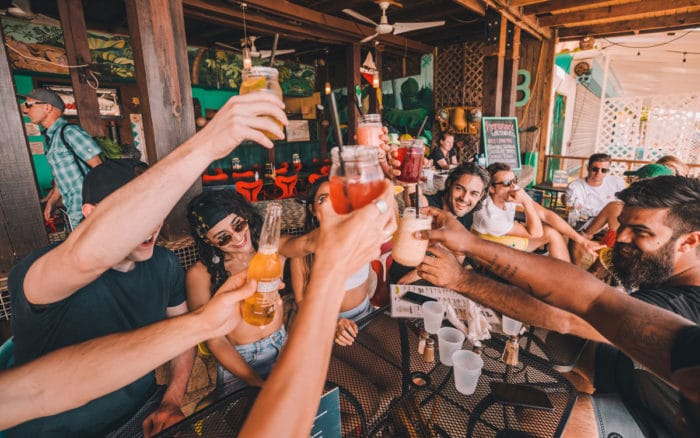"A group of people raising their glasses for a ""Cheers"""