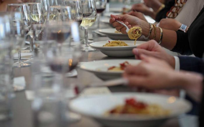 A closeup of the dining setup with wine and food