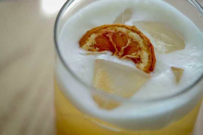 A closeup of an orange beverage with an orange slice in it