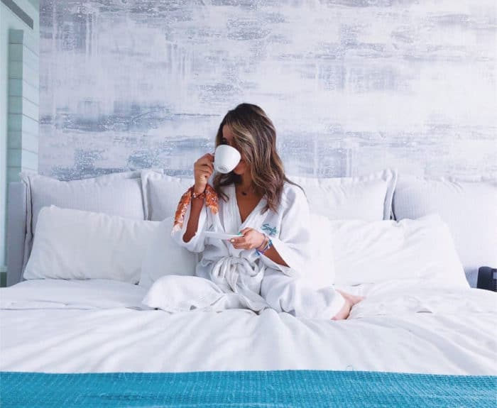 A woman drinking coffee in bed at the Condado Ocean Club