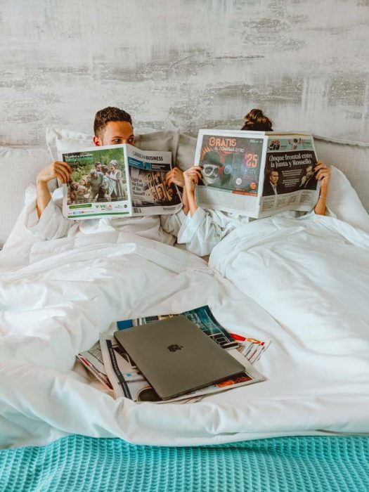 A couple in bed reading newspapers