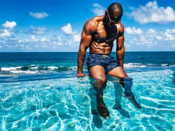 Man in swim trunks sitting on the edge of the infinity pool at Condado Ocean Club
