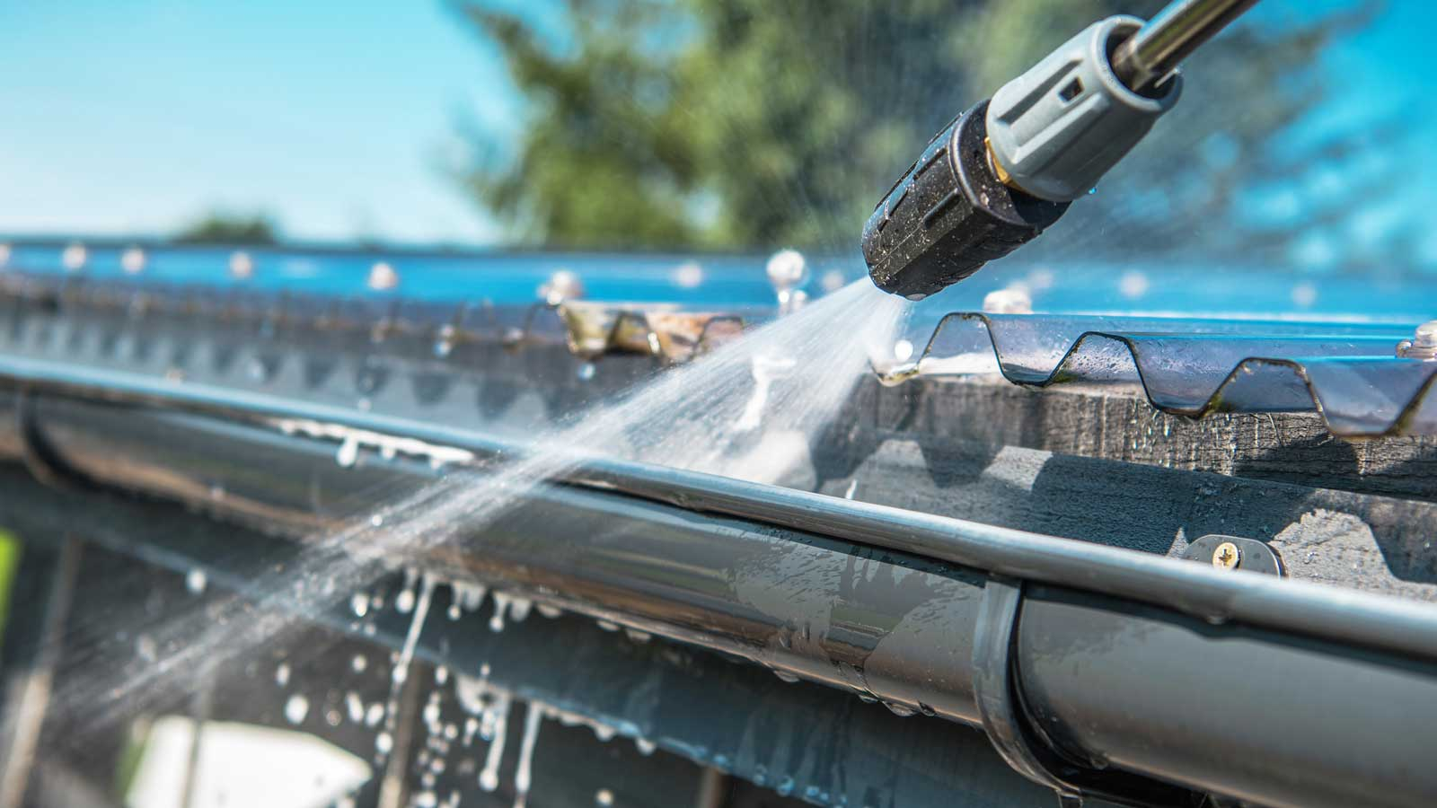 Close up of power-washing wand tip spraying water into a gutter.