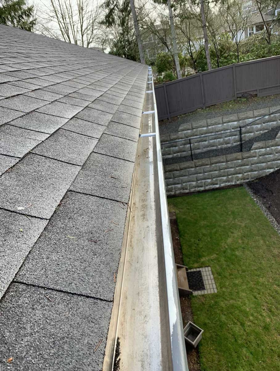 View of clean gutters on left above yard on right.