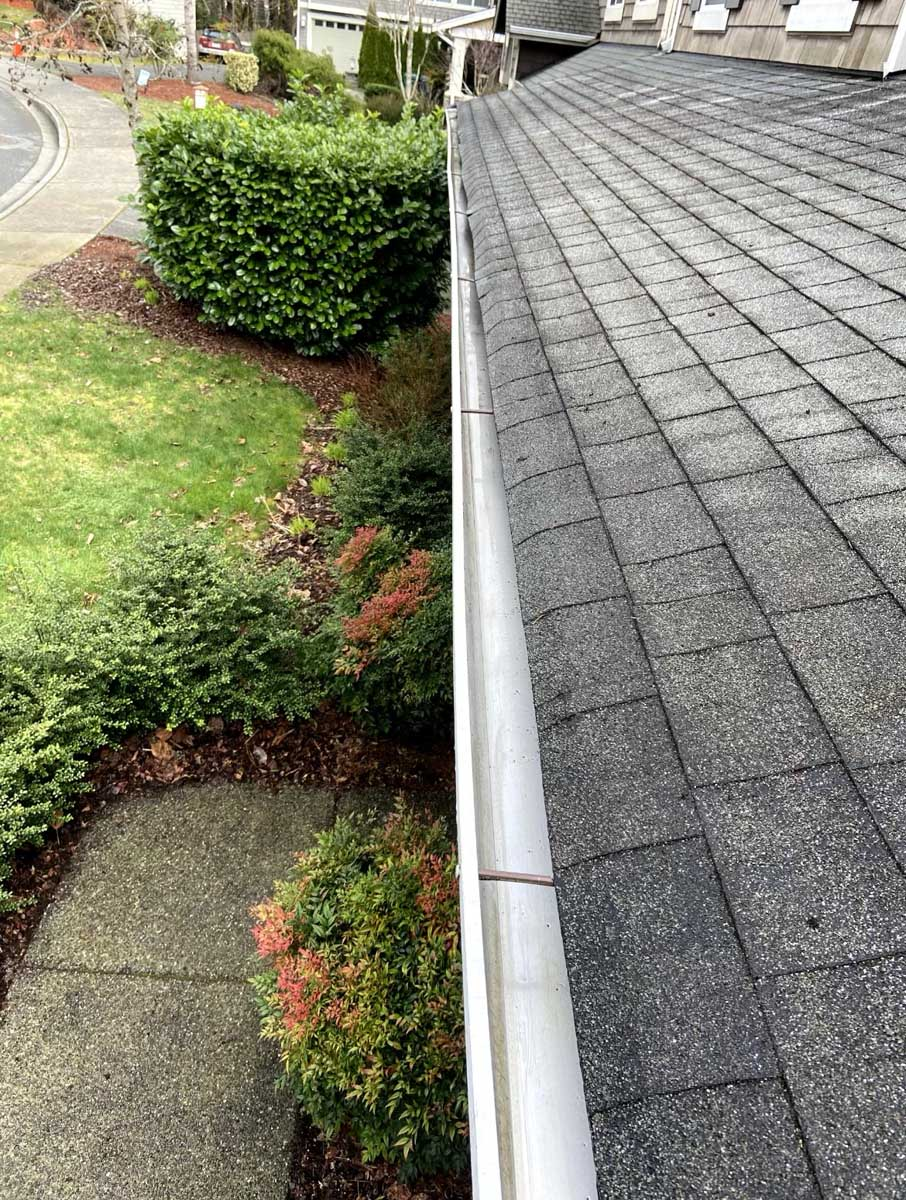 View of clean gutters above a patio and shrub