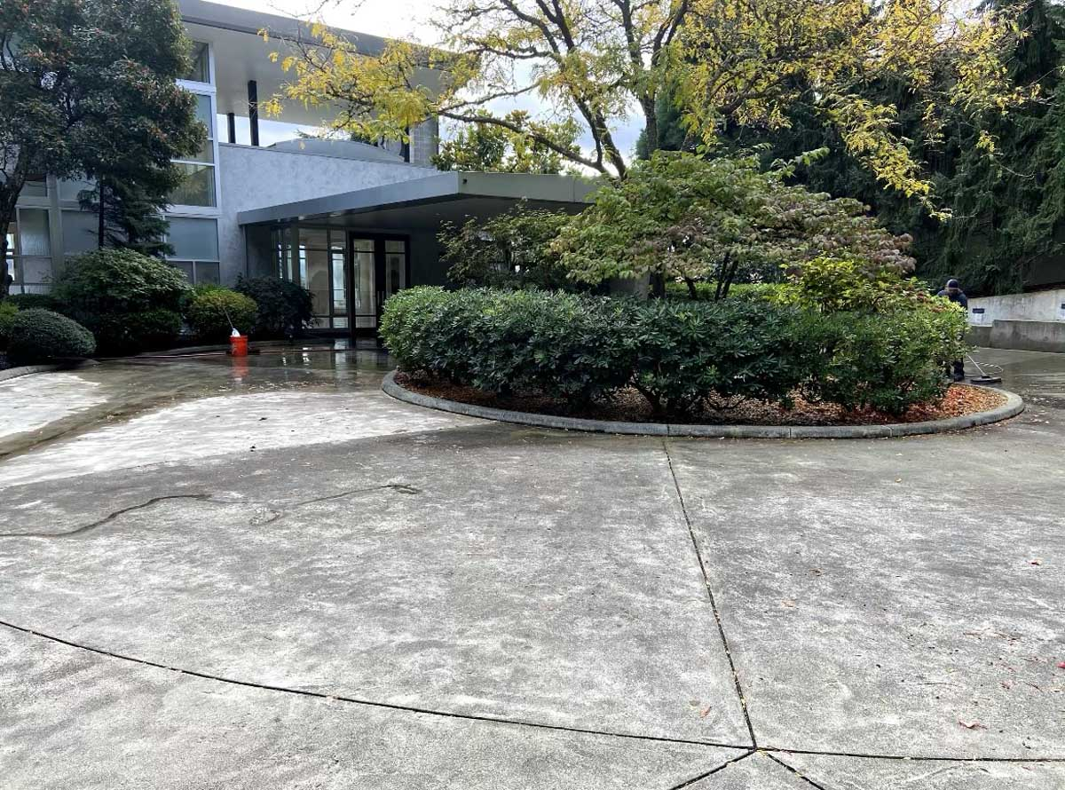 Business portico and circular drive being pressure washed.