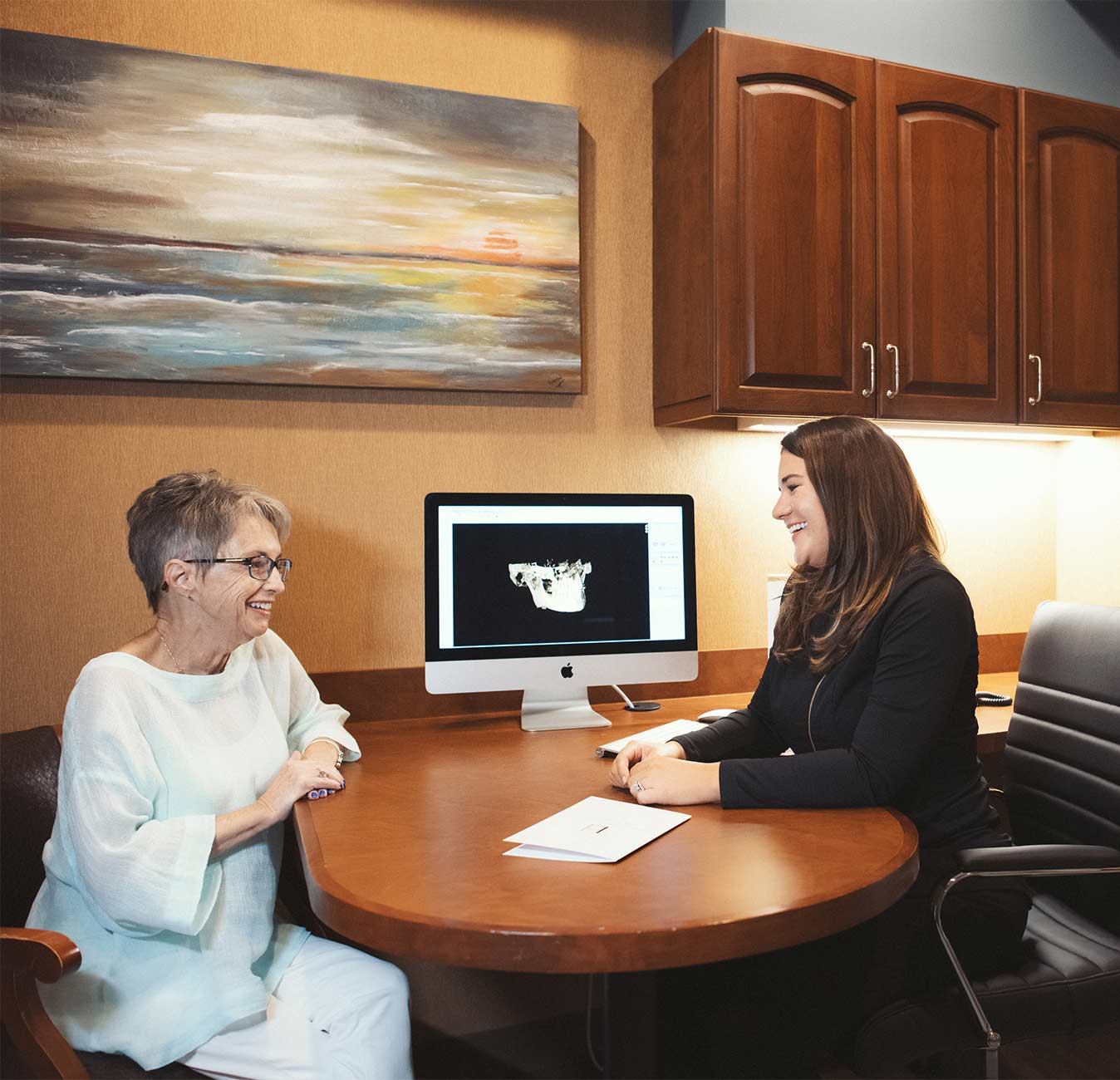 Photo of Dr. Boren and a patient sitting at a desk looking at a computer screen