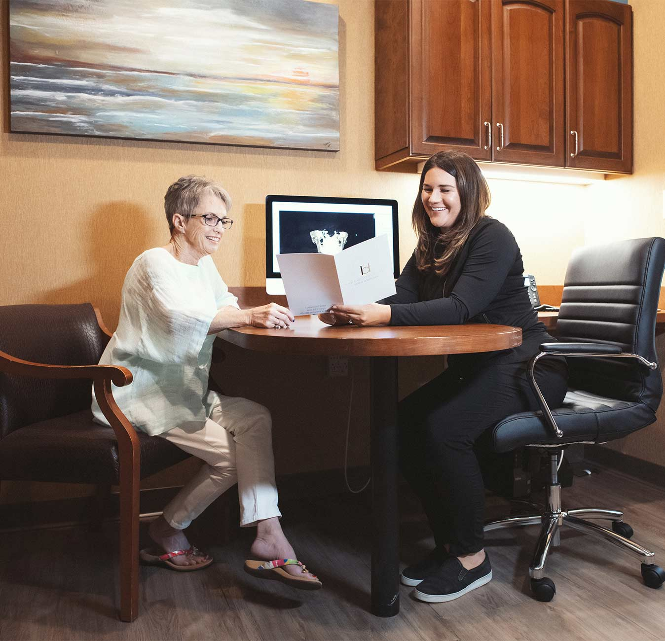 Photo of Dr. Boren and a patient sitting at a desk looking at a treatment plan folder