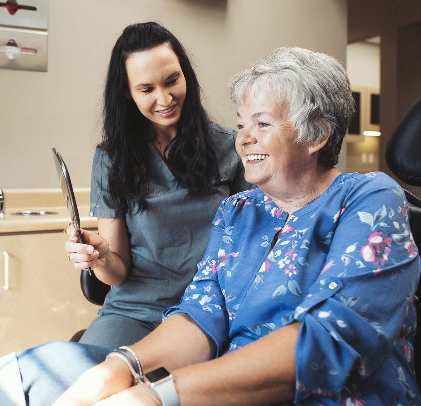 Photo of a team member holding up a mirror for a patient to see herself in